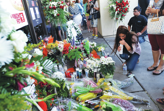 People gather around a make shift memorial created at CiCi's Pizza at 309 N. Nellis Blvd. on Monday, June 9, 2014.  Las Vegas police officers Alyn Beck and Igor Soldo were shot and killed on Sunda ...