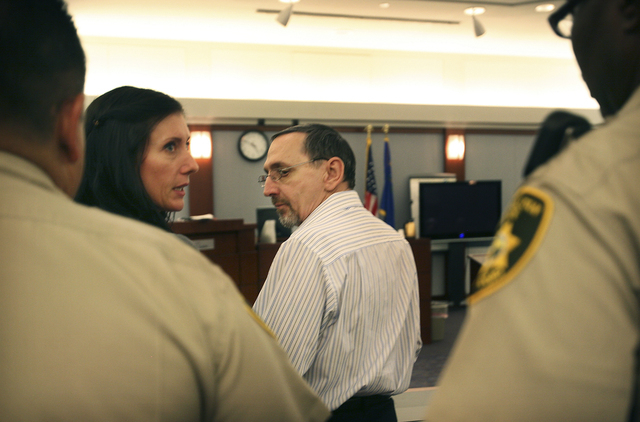 Charles Conner, center, looks back towards his attorney Andrea Luem as she speaks to court bailiffs in Clark County District Court on Wednesday, July 21, 2010, shortly before the reading of the ve ...