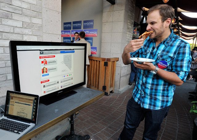 Alex DeRosa watches a video monitor for election results during a watch party for Mark Hutchison at Dom DeMarco's Pizzeria & Bar on Tuesday, June 10, 2014. (David Becker/Las Vegas Review-Journal)