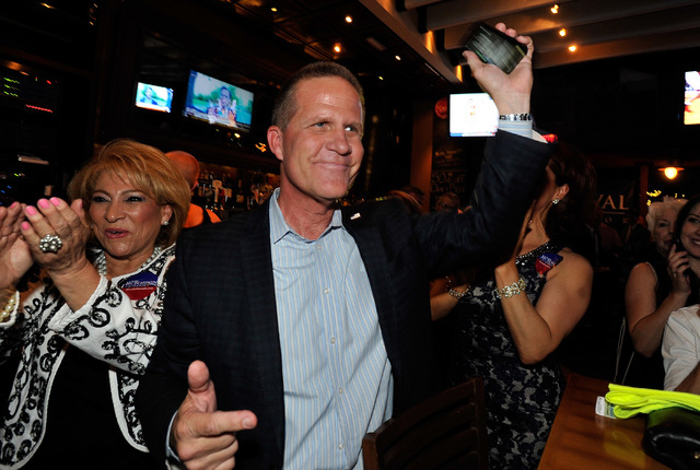 State Sen. Mark Hutchison, R-Las Vegas, raises his phone after speaking with Nev. Gov. Brian Sandoval during his election returns watch party at Dom DeMarco's Pizzeria & Bar on Tuesday, June 10, 2 ...