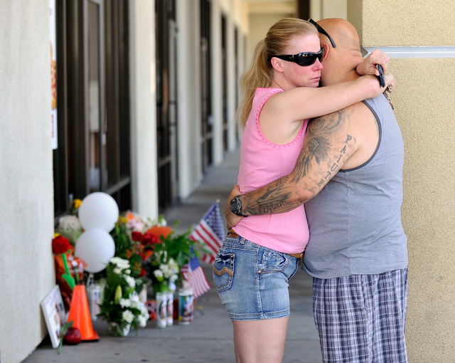 A couple hugs near a makeshift memorial near the front door of CiCi's Pizza at 309 N. Nellis Blvd. on Monday, June 9, 2014.  Las Vegas police officers Alyn Beck and Igor Soldo were shot and killed ...