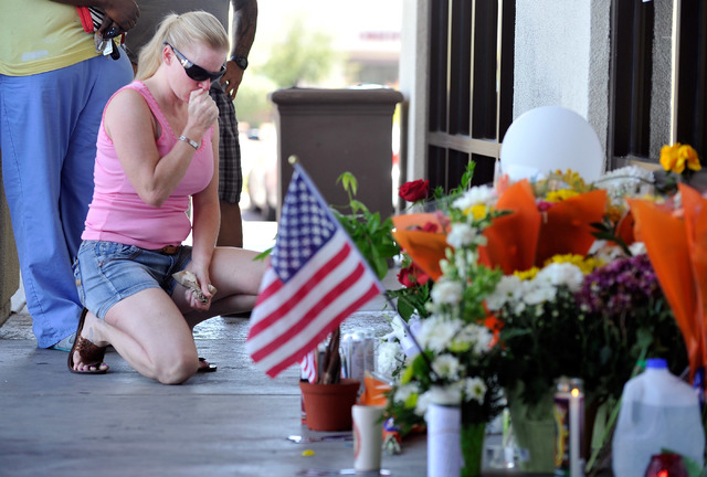 A woman pays her respects at a makeshift memorial near the front door of CiCi's Pizza at 309 N. Nellis Blvd. on Monday, June 9, 2014.  Las Vegas police officers Alyn Beck and Igor Soldo were shot  ...