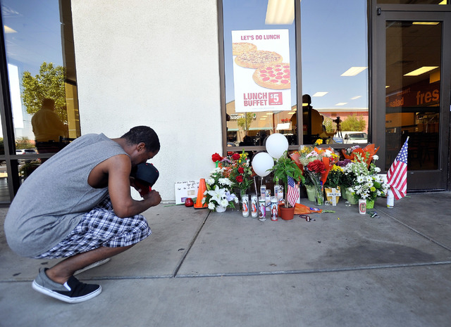 Antonio Robinson pays his respects at a makeshift memorial near the front door of CiCi's Pizza at 309 N. Nellis Blvd. on Monday, June 9, 2014.  Las Vegas police officers Alyn Beck and Igor Soldo w ...
