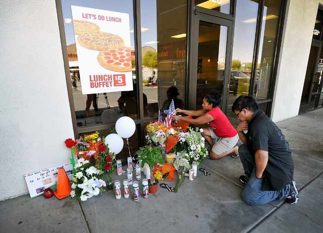 Sandra Flores, left, and Jonathan Solano pay their respects at a makeshift memorial near the front door of CiCi's Pizza at 309 N. Nellis Blvd. on Monday, June 9, 2014.  Las Vegas police officers A ...