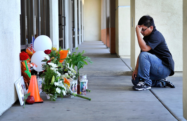 Jonathan Solano pays his respects at a makeshift memorial near the front door of CiCi's Pizza at 309 N. Nellis Blvd. on Monday, June 9, 2014.  Las Vegas police officers Alyn Beck and Igor Soldo we ...