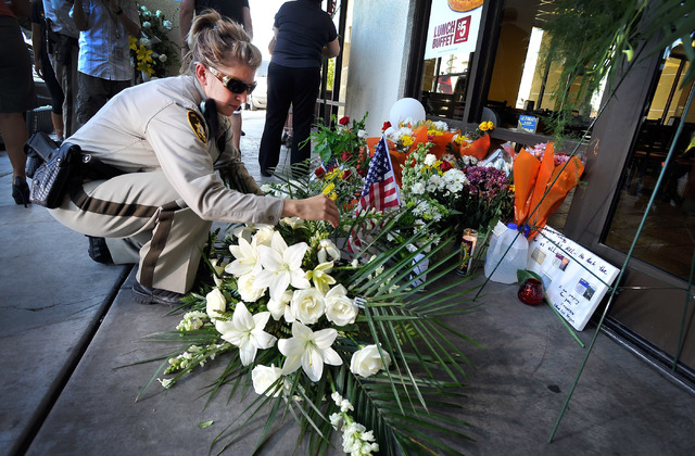 Las Vegas Police officer A. Stout places a bouquet of flowers at a makeshift memorial near the front door of CiCi's Pizza at 309 N. Nellis Blvd. on Monday, June 9, 2014.  Las Vegas police officers ...