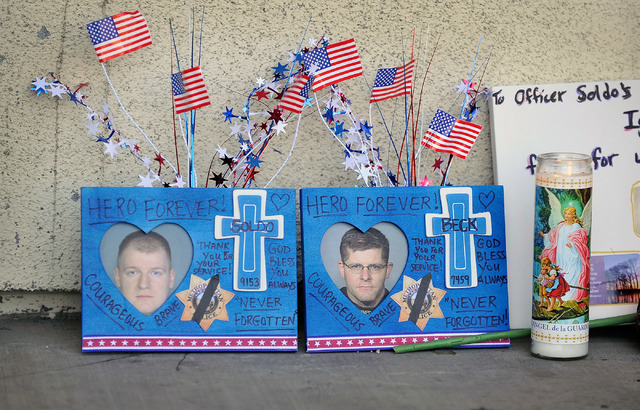 Candles, flags and other items sit at a makeshift memorial near the front door of CiCi's Pizza at 309 N. Nellis Blvd. on Monday, June 9, 2014.  Las Vegas police officers Alyn Beck and Igor Soldo w ...