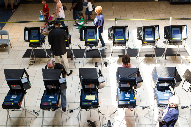 Las Vegas residents, clockwise from center right, Pat Lawrence, Aubrey Roberson, and Anders Denson cast their ballots on the first day of early voting at the Meadows Mall in Las Vegas on Saturday, ...