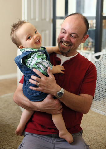 Kevin Zelenka holds his son Carter, 16 months, in his home Wednesday, May 28, 2014, in Las Vegas. Zelenka is a stay-at-home dad of twin boys and writes on his blog doulbetroubledaddy.com in his sp ...