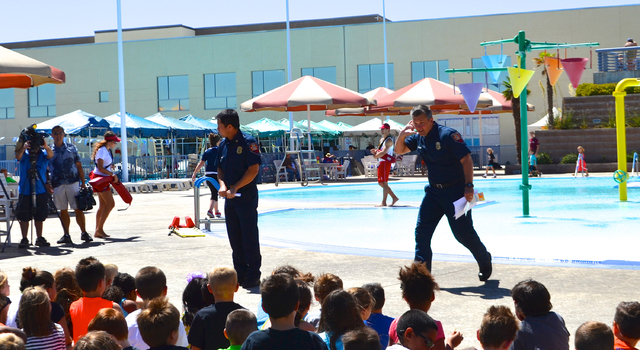 Henderson Professional Fire Fighters President Dan Pentkowski and Henderson Fire Chief Steve Goble give a presentation of the Safe Pools Rule! campaign to city of Henderson Kid Zone participants.