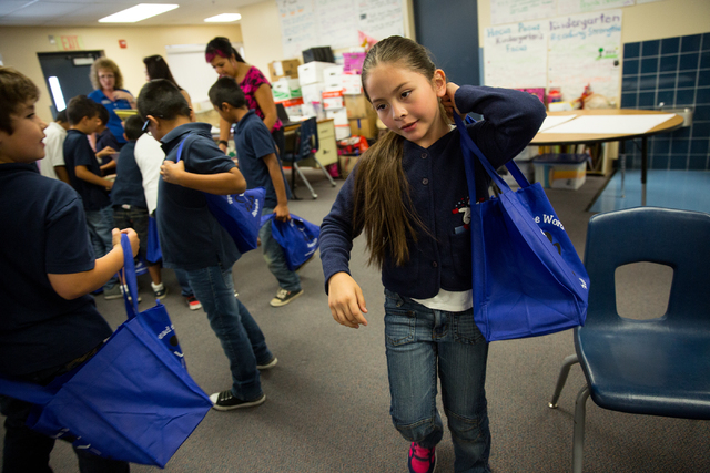Vegas Verdes Elementary School second-grader Joanne Ledesma swings a complementary tote bag full of books over her shoulder during a book donation event May 28. The school, 4000 W. El Parque Ave., ...