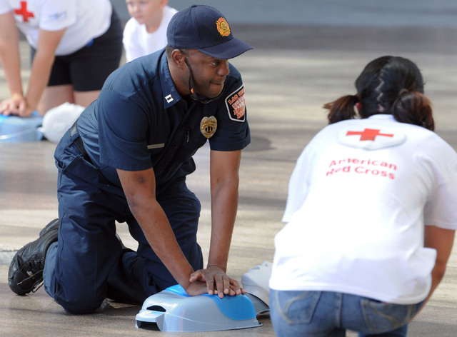 Las Vegas Fire Department Captain Lionel Newby performs CPR on a manikin front of the Third Street stage at Fremont Street Experience in downtown Las Vegas, Friday, June 6, 2014. In a flash mob ex ...