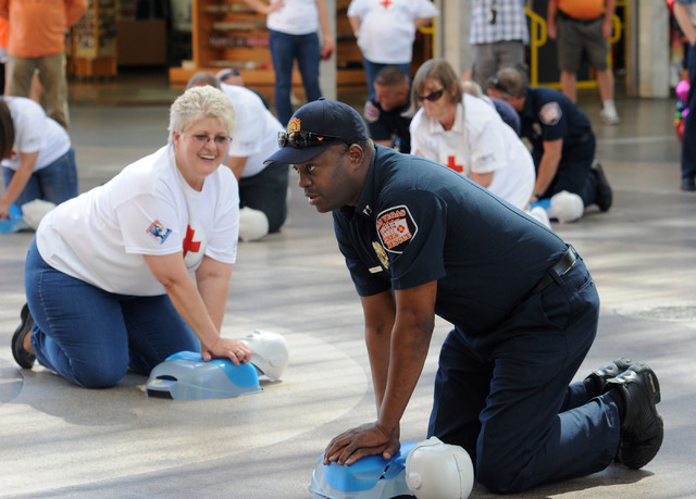 Las Vegas Fire Department Captain Lionel Newby performs CPR on a manikin front of the Third Street stage at Fremont Street Experience in downtown Las Vegas, Friday, June 6, 2014.  In a flash mob e ...