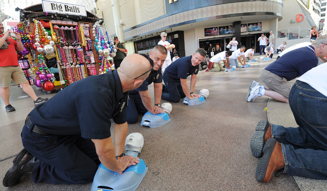 Las Vegas Firefighters Michael Olivas, David Lopez and Dan Wilder, left to right, perform CPR on manikins in front of the Third Street stage at Fremont Street Experience in downtown Las Vegas, Fri ...