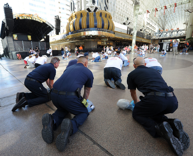 Las Vegas Firefighters, Dan Wilder, David Lopez and Michael Olivas, left to right backs to camera, perform CPR on manikins in front of the Third Street stage at Fremont Street Experience in downto ...