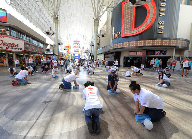 Las Vegas Fire Captain Lionel Newby, center right, performs CPR on a manikin while surrounded by American Red Cross volunteers in front of the Third Street stage at Fremont Street Experience in do ...