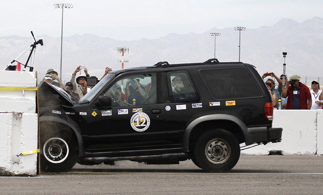 A Ford Explorer is crashed into a barrier at around 40 mph while bystanders take photos during the 13th annual ARC-CSI conference at the Las Vegas Motor Speedway on Monday, June 2, 2014. The confe ...