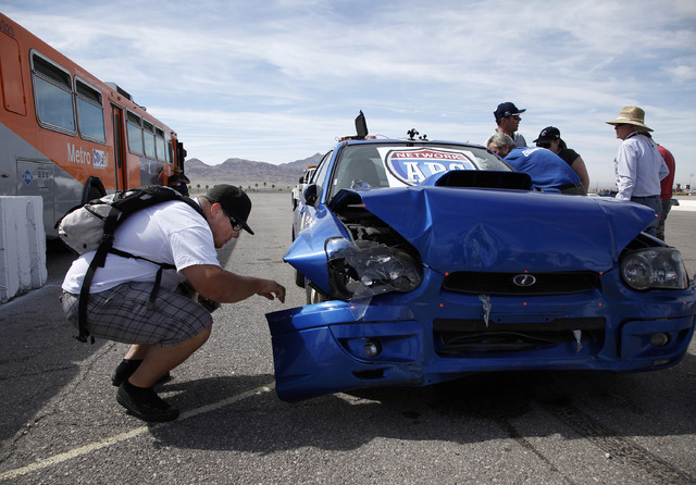 Matthew Padilla, a law enforcement officer from Orange County, inspects a Subaru after it crashed into a barrier at around 35 mph during the 13th annual ARC-CSI conference at the Las Vegas Motor S ...