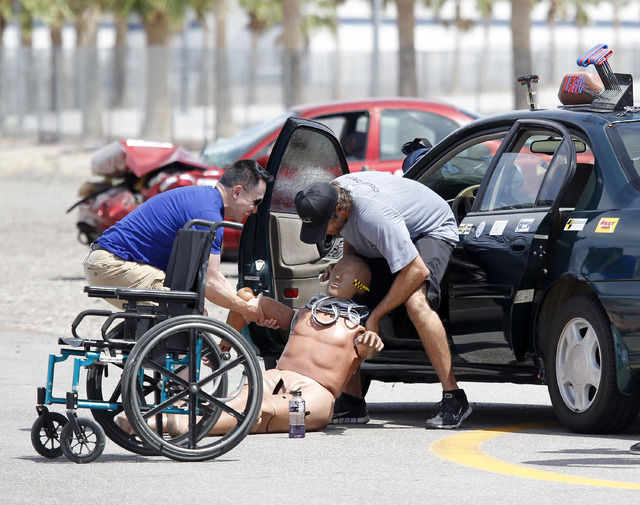 Crew members load a crash test dummy with sensors into a car during the 13th annual ARC-CSI conference at the Las Vegas Motor Speedway on Monday, June 2, 2014. The conference brings together leade ...