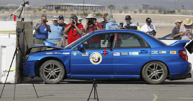 A Subaru is crashed into a barrier at around 35 mph while bystanders take photos during the 13th annual ARC-CSI conference at the Las Vegas Motor Speedway on Monday, June 2, 2014. The conference b ...