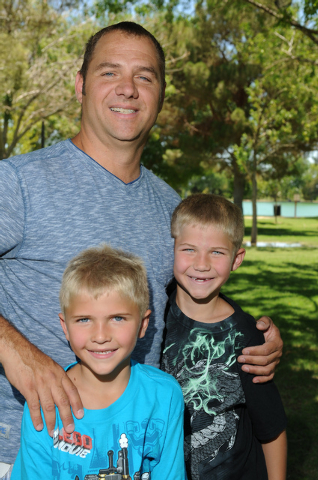 Christopher Beaumont, center, poses for a portrait with his two sons Tre, right, 9, and Bronson, 7, at Sunset Park in Las Vegas Saturday, May 31, 2014. Beaumont, a single father, is an organizer f ...