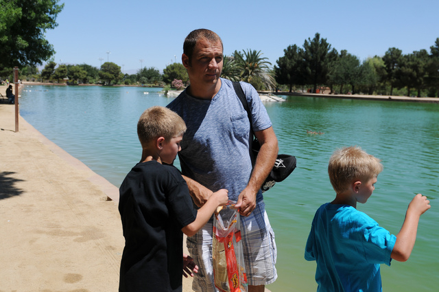 Christopher Beaumont, center, feeds the birds with his two sons Bronson, right, 7, and Tre, 9, at Sunset Park in Las Vegas Saturday, May 31, 2014. Beaumont, a single father, is an organizer for Si ...