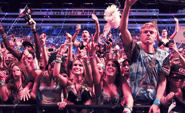 Attendees react as Diplo performs at the Cosmic Meadow stage at the Electric Daisy Carnival at the Las Vegas Motor Speedway in Las Vegas during the early hours of Saturday, June 21, 2014. (Chase S ...