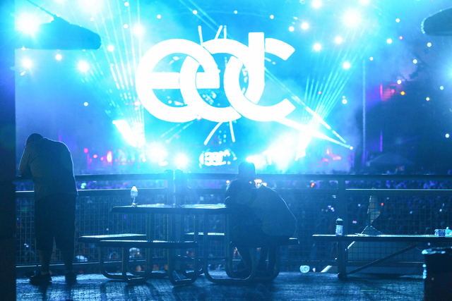 Attendees take a break as Luciano performs at the Neon Garden stage in the backgroundat the Electric Daisy Carnival at the Las Vegas Motor Speedway in Las Vegas during the early hours of Saturday, ...