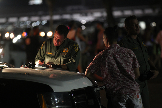 A Las Vegas police officer rights a citation as a man waits outside of the Electric Daisy Carnival at the Las Vegas Motor Speedway in Las Vegas on Friday, June 20, 2014. (Chase Stevens/Las Vegas R ...