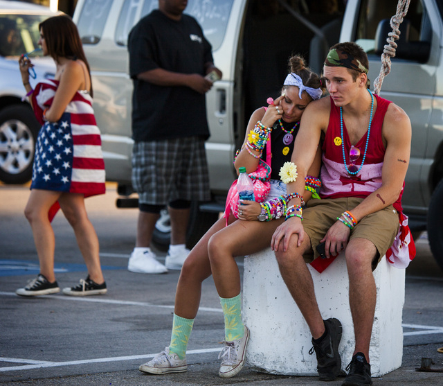 Juliana Feinberg,left, and Spencer Swinston, both from Calgary, Can. relax  after a night at Electric Daisy Carnival at Las Vegas Motor Speedway on Monday, June 23, 2014.  EDC drew 134,000 people  ...