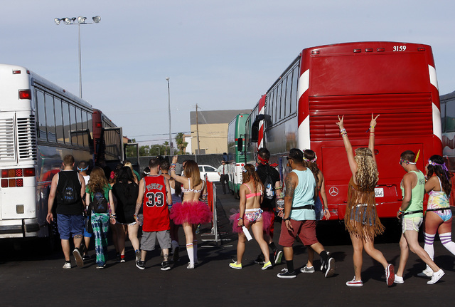 Festival goers load onto busses on the Strip across from the Luxor hotel-casino for a ride to the first night of the Electric Daisy Carnival at the Las Vegas Motor Speedway in Las Vegas on Friday, ...