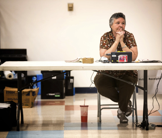 Election worker Barbara Burgess  waits for voters  at D'Vorre & Hal Ober Elementary School at 3035 Desert Marigold Lane on Tuesday, June 10, 2014. Election officials are expecting a low turn out i ...
