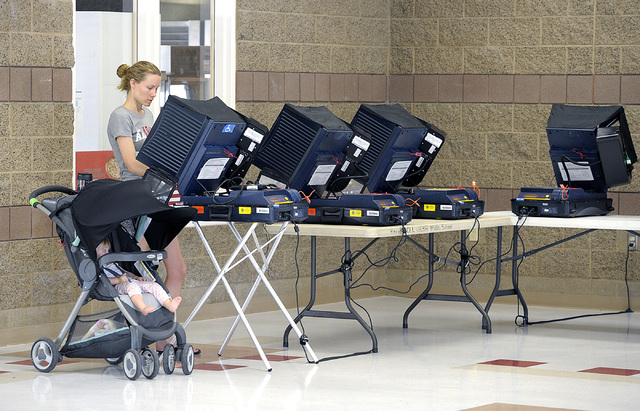Canella Kircher, accompanied by her 11-month old daughter Sienna, casts her vote in the polling place at Del E. Webb Middle School in Anthem on Tuesday, June 10, 2014. By 8:30am, 29 voters had cas ...