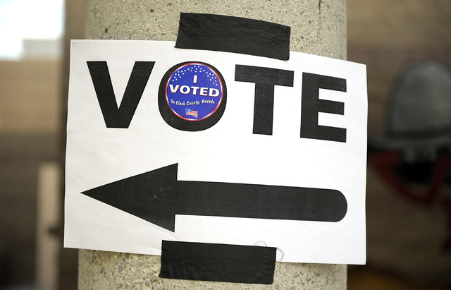 """A directional sign is embellished with an """"I voted"""" sticker at Del E. Webb Middle School in Anthem on Tuesday, June 10, 2014. By 8:30am, 29 voters had cast their votes at the Webb school ..."""