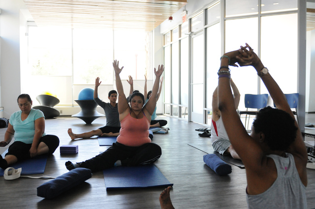 Students take directions from yoga instructor Chidimma Ozor during a class at Turntable Health, June 9. (Erik Verduzco/View)