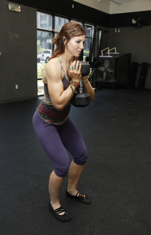 Trainer Laura Salcedo demonstrates the finishing position for a squat with a dumbbell at CrossFit Mountain's Edge in Las Vegas on Tuesday, May 27, 2014. (Justin Yurkanin/Las Vegas Review-Journal)