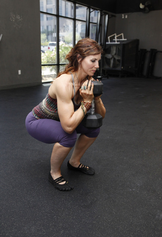 Trainer Laura Salcedo demonstrates the middle position for a squat with a dumbbell at CrossFit Mountain's Edge in Las Vegas on Tuesday, May 27, 2014. (Justin Yurkanin/Las Vegas Review-Journal)