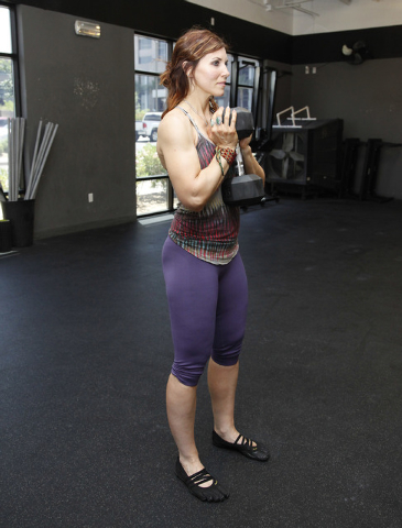 Trainer Laura Salcedo demonstrates the starting position for a squat with a dumbbell at CrossFit Mountain's Edge in Las Vegas on Tuesday, May 27, 2014. (Justin Yurkanin/Las Vegas Review-Journal)