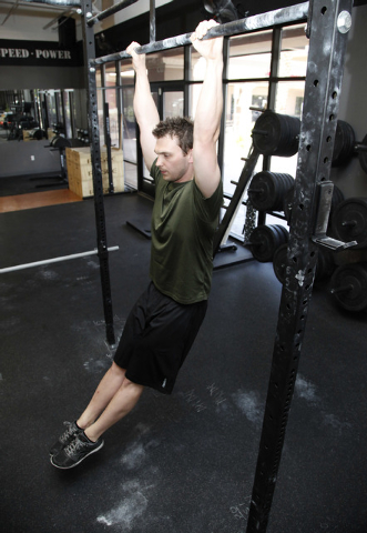 Trainer Chris Huth demonstrates the starting position position for a k to elbow pull up bar exercise CrossFit Mountain's Edge in Las Vegas on Tuesday, May 27, 2014. (Justin Yurkanin/Las Vegas Revi ...