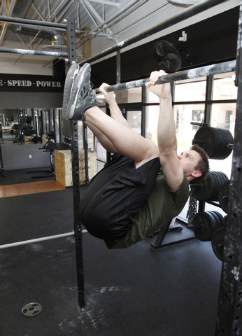 Trainer Chris Huth demonstrates the finishing position position for a k to elbow pull up bar exercise CrossFit Mountain's Edge in Las Vegas on Tuesday, May 27, 2014. (Justin Yurkanin/Las Vegas Rev ...
