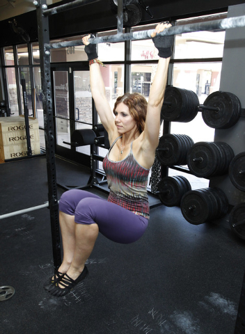Trainer Laura Salcedo demonstrates the finishing position for a k to waist pull up bar exercise CrossFit Mountain's Edge in Las Vegas on Tuesday, May 27, 2014. (Justin Yurkanin/Las Vegas Review-Jo ...