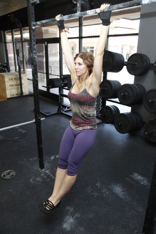 Trainer Laura Salcedo demonstrates the starting position for a k to waist pull up bar exercise CrossFit Mountain's Edge in Las Vegas on Tuesday, May 27, 2014. (Justin Yurkanin/Las Vegas Review-Jou ...