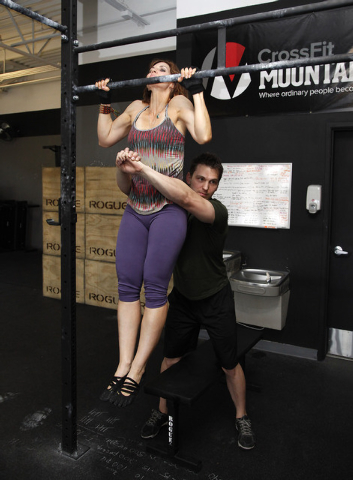 Trainers Laura Salcedo and Chris Huth demonstrates the starting position for a partner  pull up bar exercise CrossFit Mountain's Edge in Las Vegas on Tuesday, May 27, 2014. (Justin Yurkanin/Las Ve ...