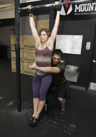 Trainers Laura Salcedo and Chris Huth demonstrates the finishing position for a partner  pull up bar exercise CrossFit Mountain's Edge in Las Vegas on Tuesday, May 27, 2014. (Justin Yurkanin/Las V ...