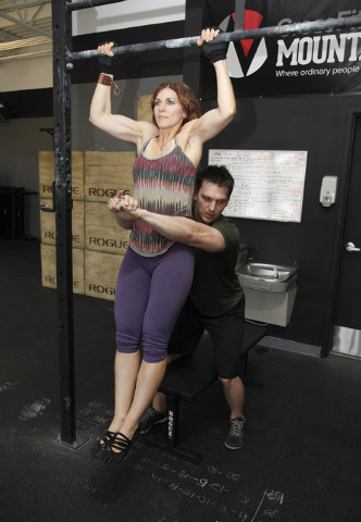 Trainers Laura Salcedo and Chris Huth demonstrates the middle position for a partner  pull up bar exercise CrossFit Mountain's Edge in Las Vegas on Tuesday, May 27, 2014. (Justin Yurkanin/Las Vega ...