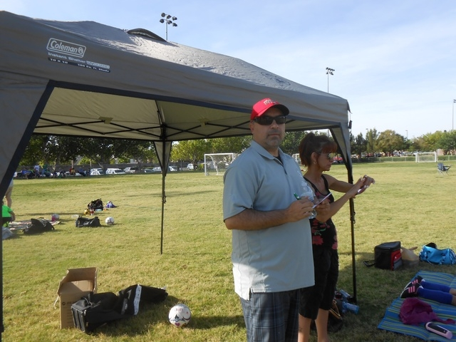 Ruben Benavidez coaches his daughter's soccer team May 17 from the shade of a pop-up tent at The Crossing Park. Beside him is his wife, Katie, who said her husband is always encouraging and very i ...
