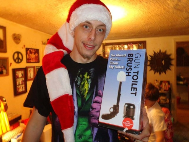 """Jerad Miller holds a gag gift -- a """"gun toilet brush"""" -- in this photo posted to Amanda Miller's Facebook page. (Courtesy, Facebook)"""