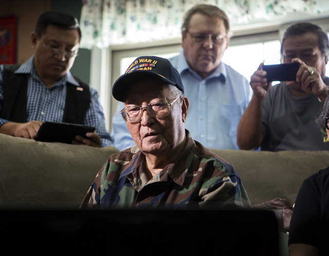 Filipino-American World War II veteran Anastacio Sumajit watches the Committee on Armed Services hearing live stream on a computer, Tuesday, June 24, 2014. Behind Sumajit is his son Romeo Sumajit, ...