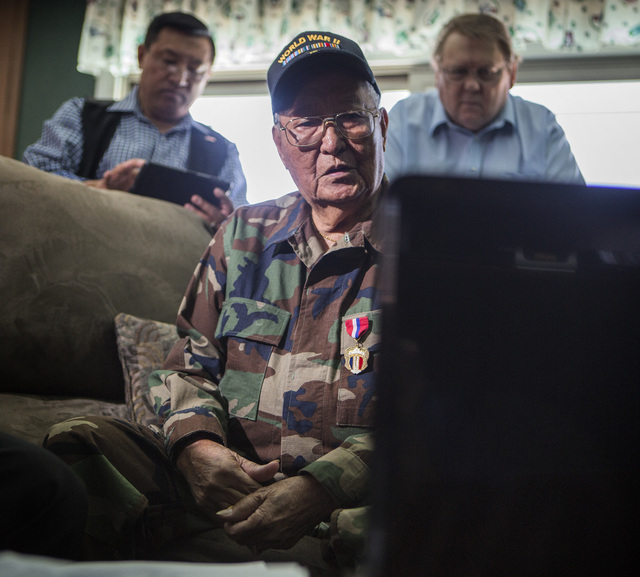 Filipino-American World War II veteran Anastacio Sumajit watches the Committee on Armed Services hearing live stream on  a computer, Tuesday, June 24, 2014. Behind Sumajit is his Caesar Elpidio, l ...