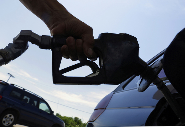 In this June 11, 2013, file photo, a motorist puts fuel in his car's gas tank at a service station in Springfield, Ill. The price of gasoline will go up in the Las Vegas Valley soon when local fue ...